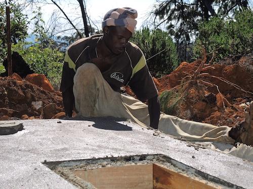 Mr Farai plastering the septic tank